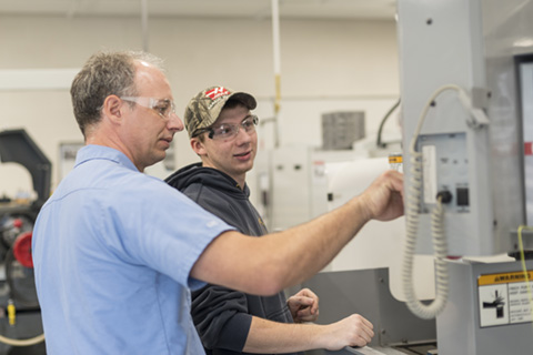 Logan working with an instructor in the CNC lab.