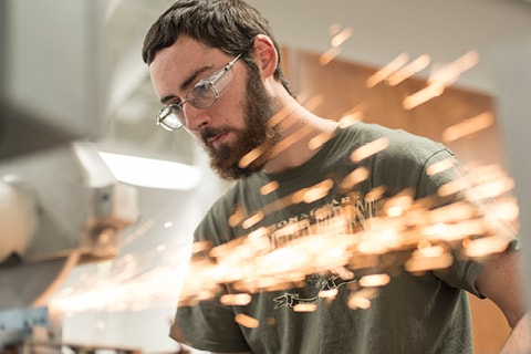 Student in trades lab with sparks flying.
