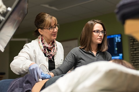 Sonography Faculty with a student working in the lab.