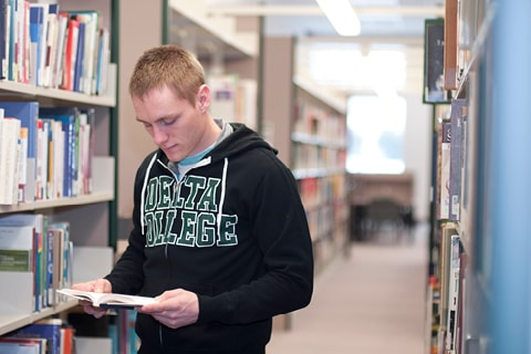 Student looking at books in Library rows