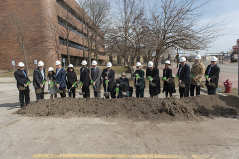 A group of local administrators at the site of the new Saginaw Center wearing hard hats and holding shovels.