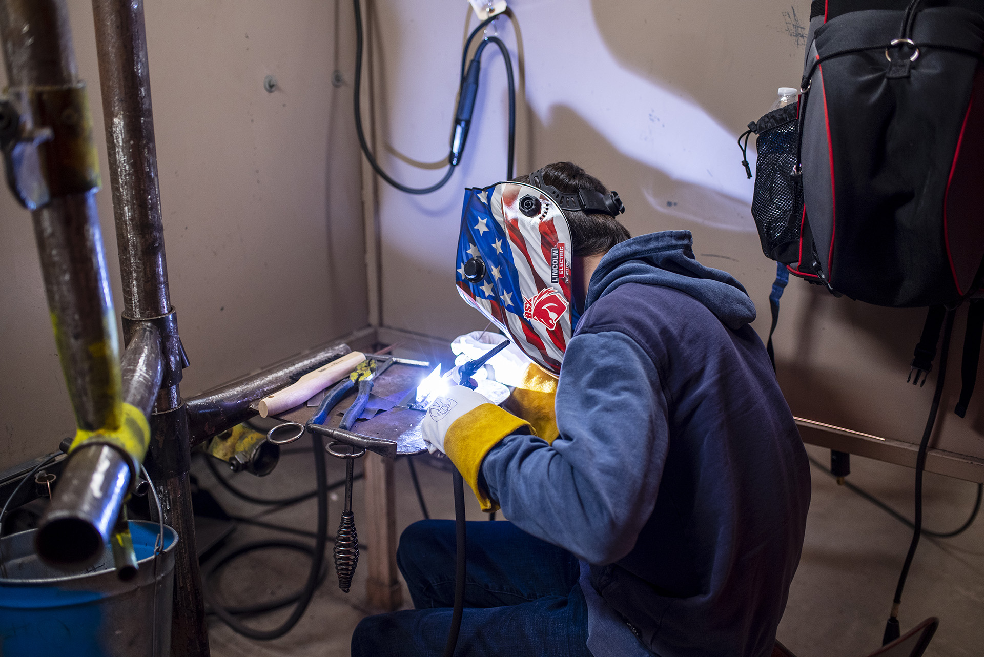 Outfitted in his protective mask, a student fine tunes his welding skills.