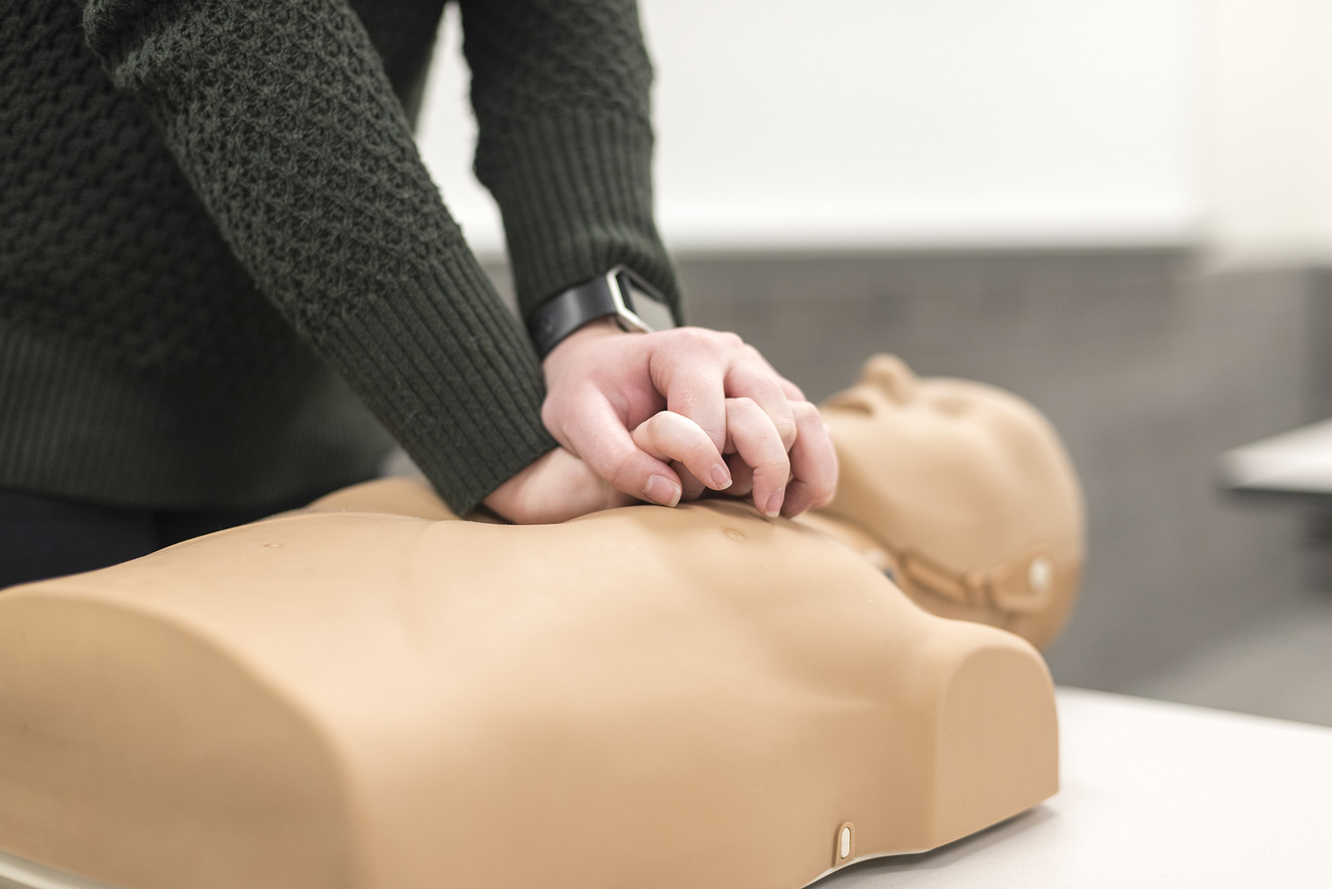 Student practicing on adult CPR manikin