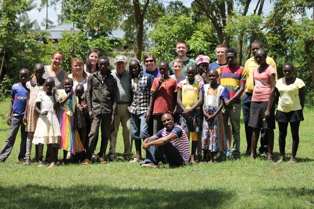 A group of Delta staff and students with villagers in Kenya
