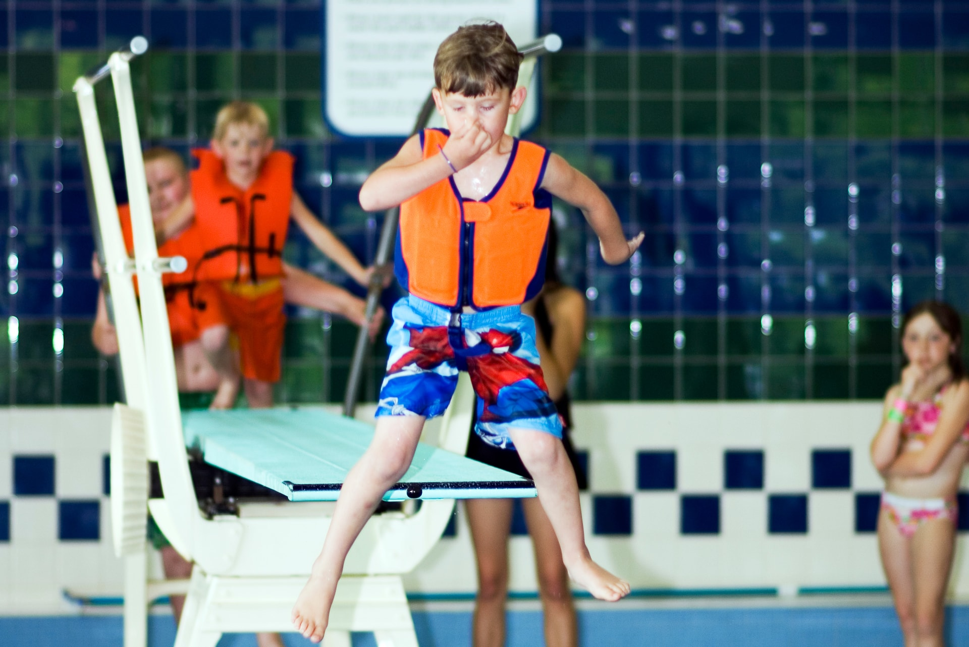 Child jumping off diving board.
