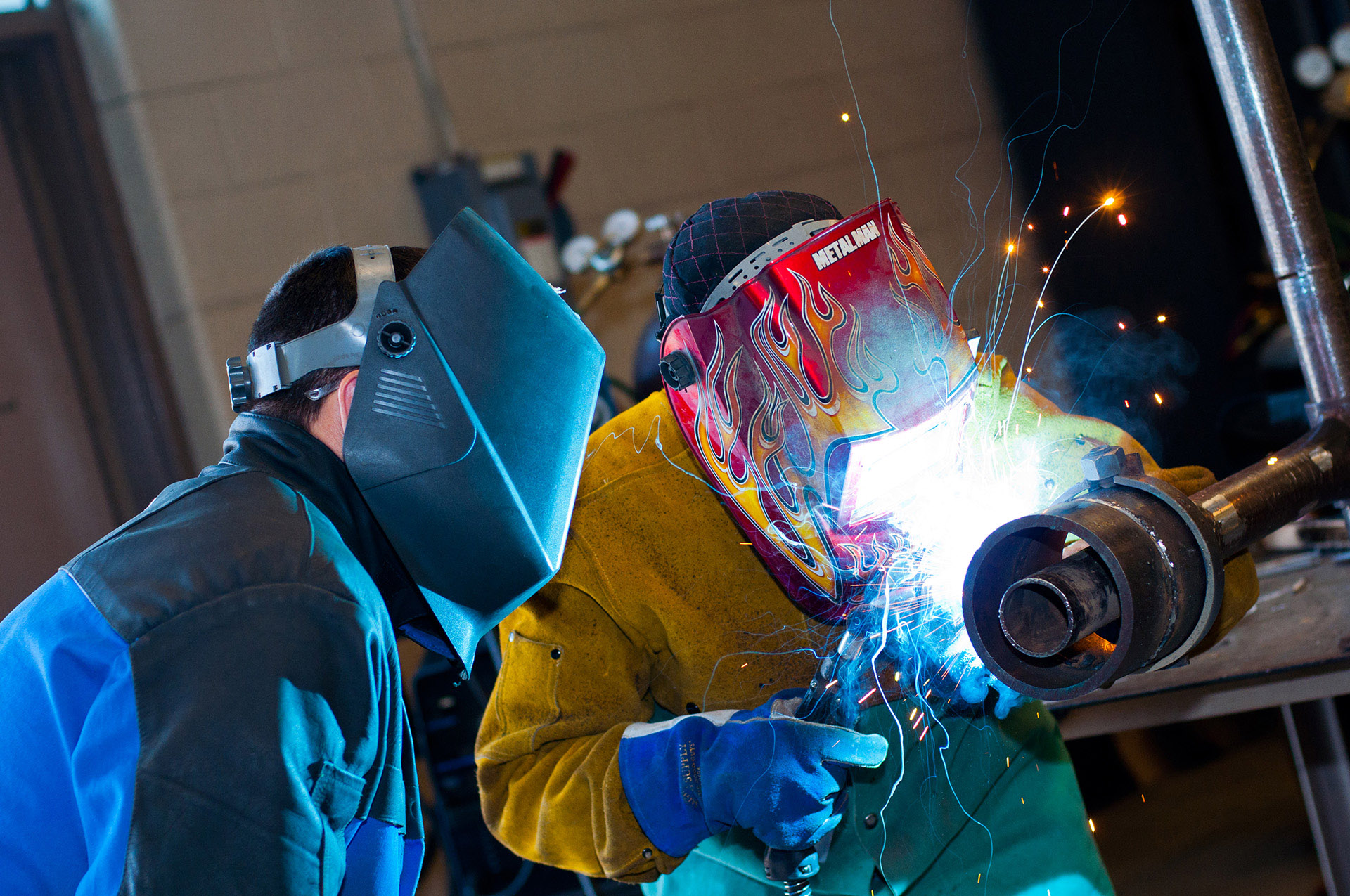 Two students welding with sparks flying